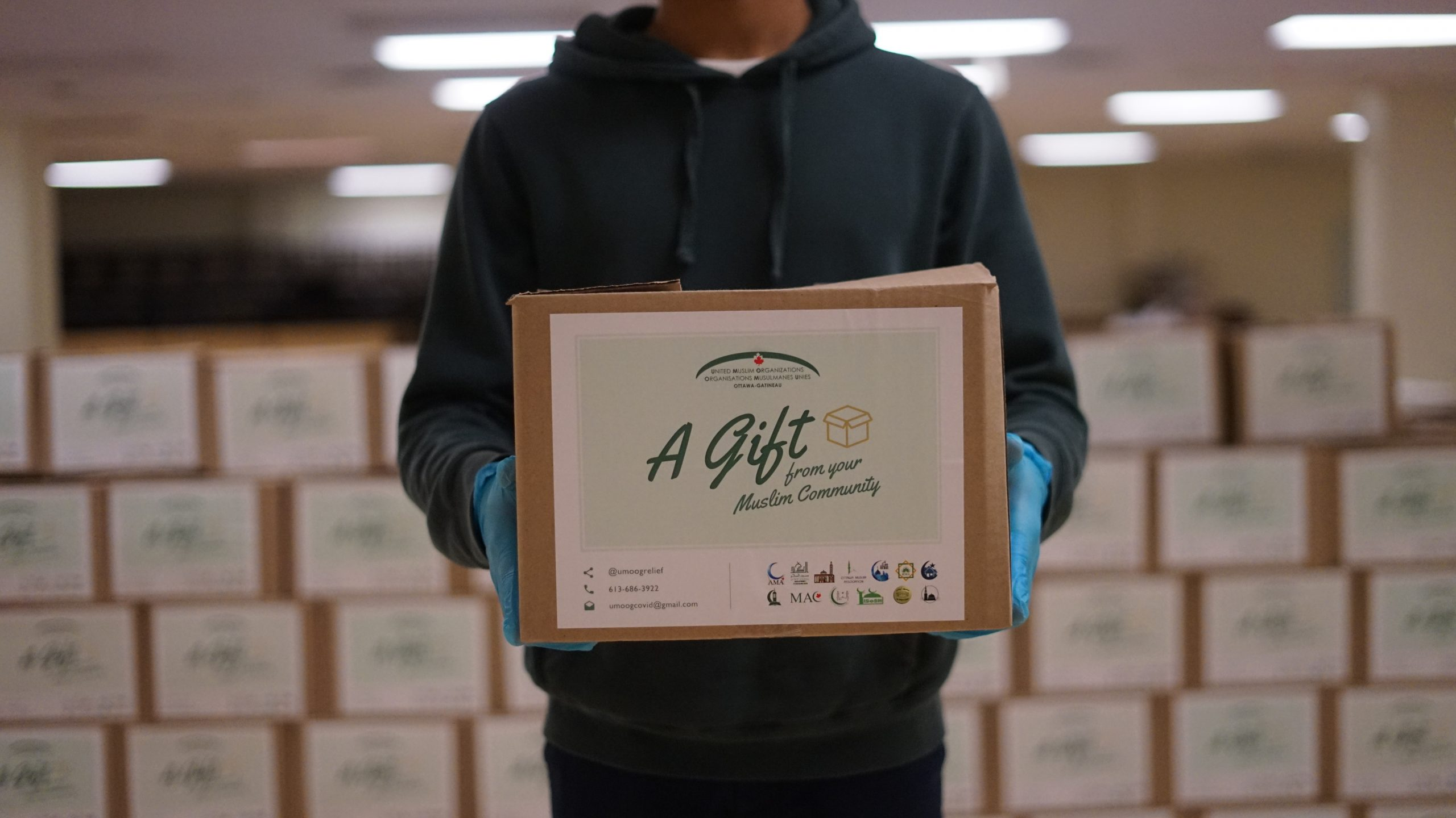 """A person holds a box filled with food that says """"A gift from your Muslim community"""""""