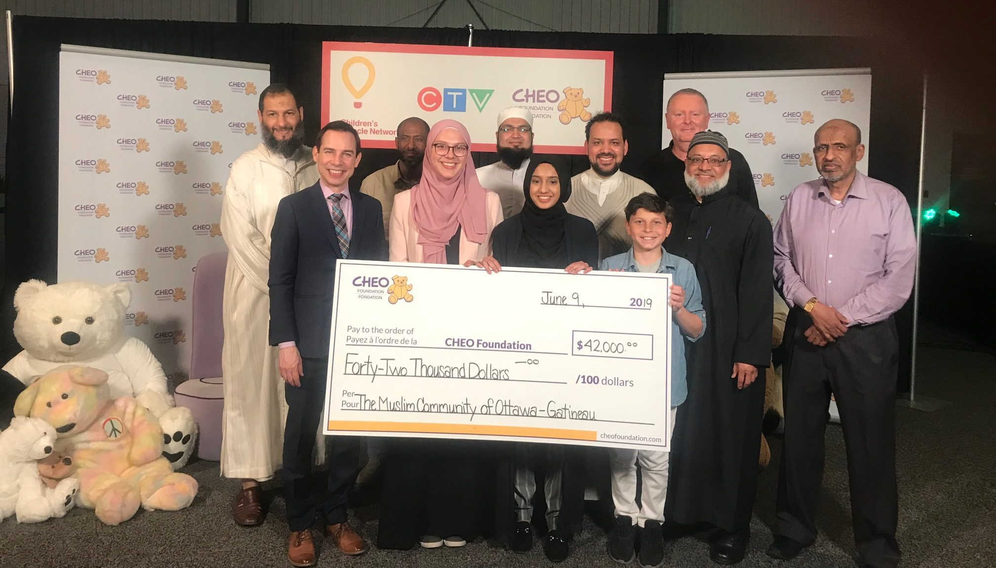 A group of people holding a cheque to CHEO