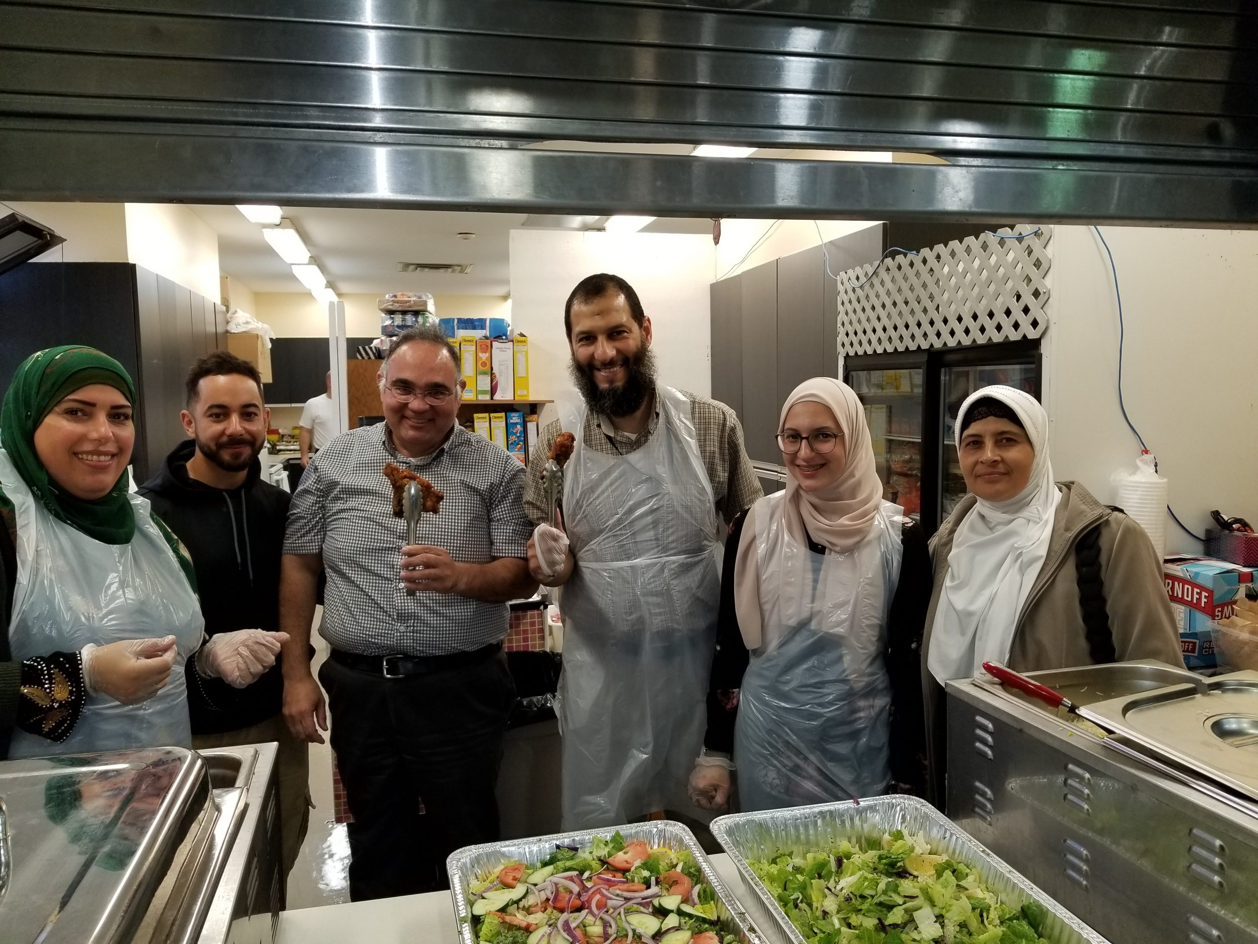 Six people standing in a kitchen, ready to serve food.