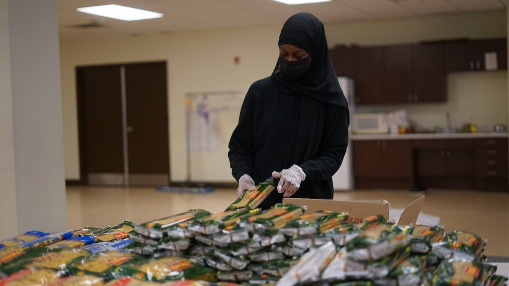 A volunteer puts pasta in an aid box