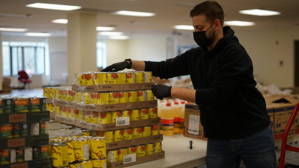 A volunteer reaches towards stacked pallets of canned food