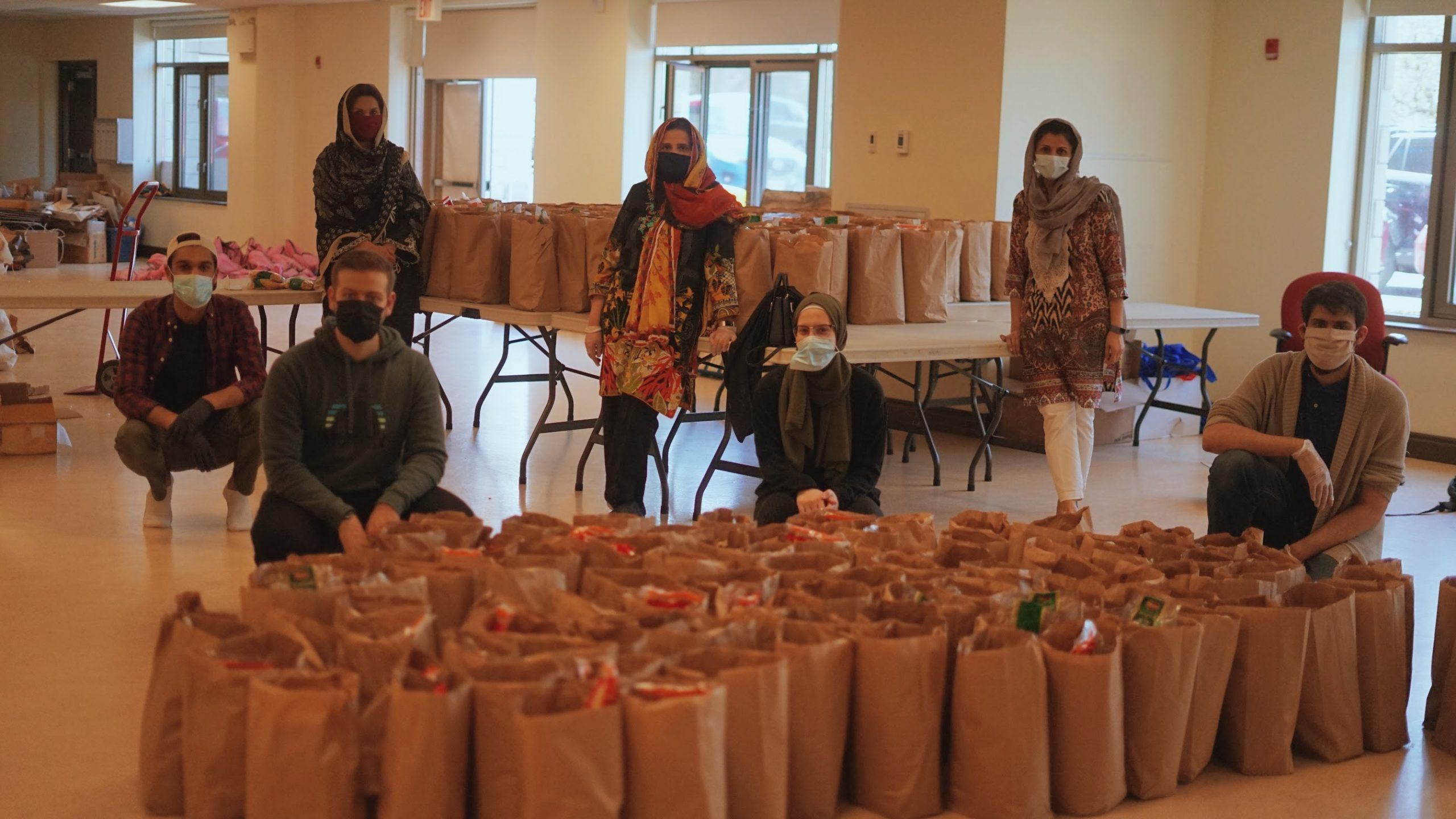 7 volunteers pose (socially distanced) in front of packed aid bags