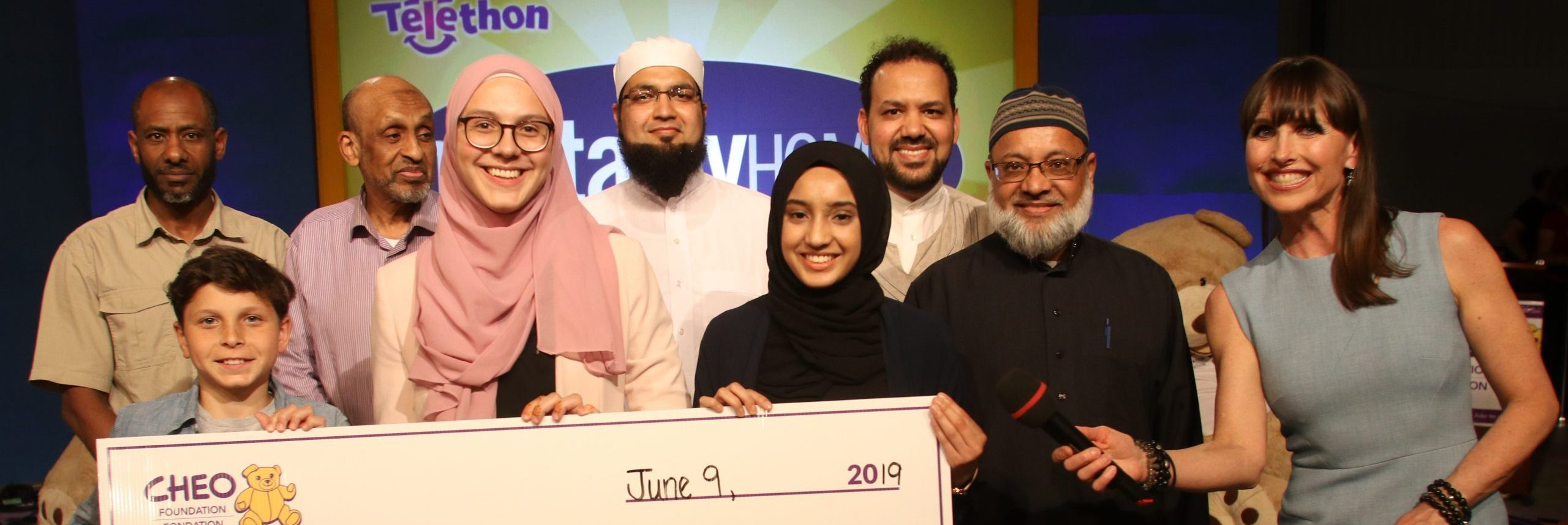 A group of people hold a cheque made out to CHEO