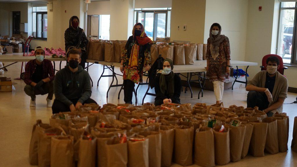 Volunteers sit and stand behind packed bags