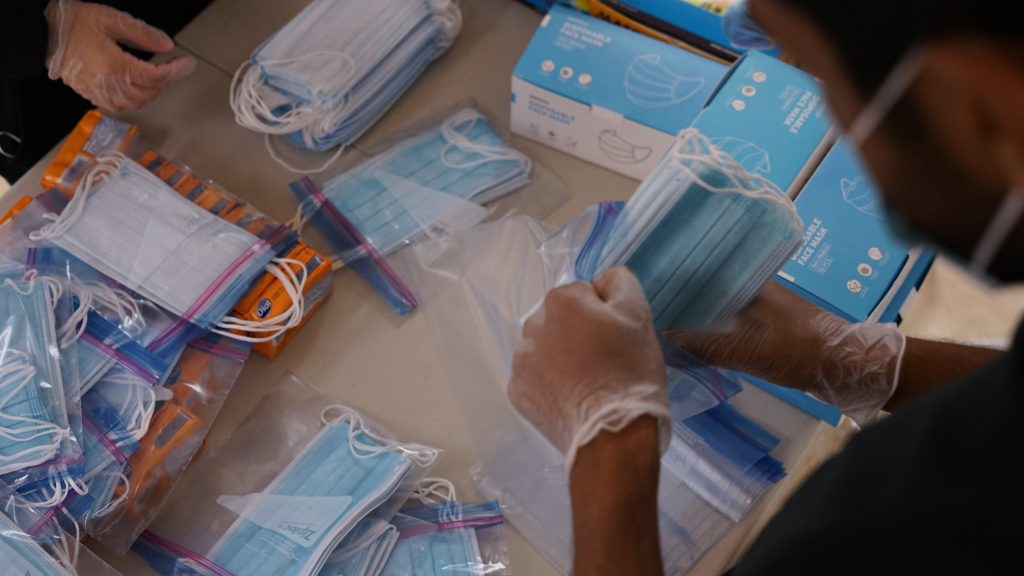People packing masks into ziploc bags