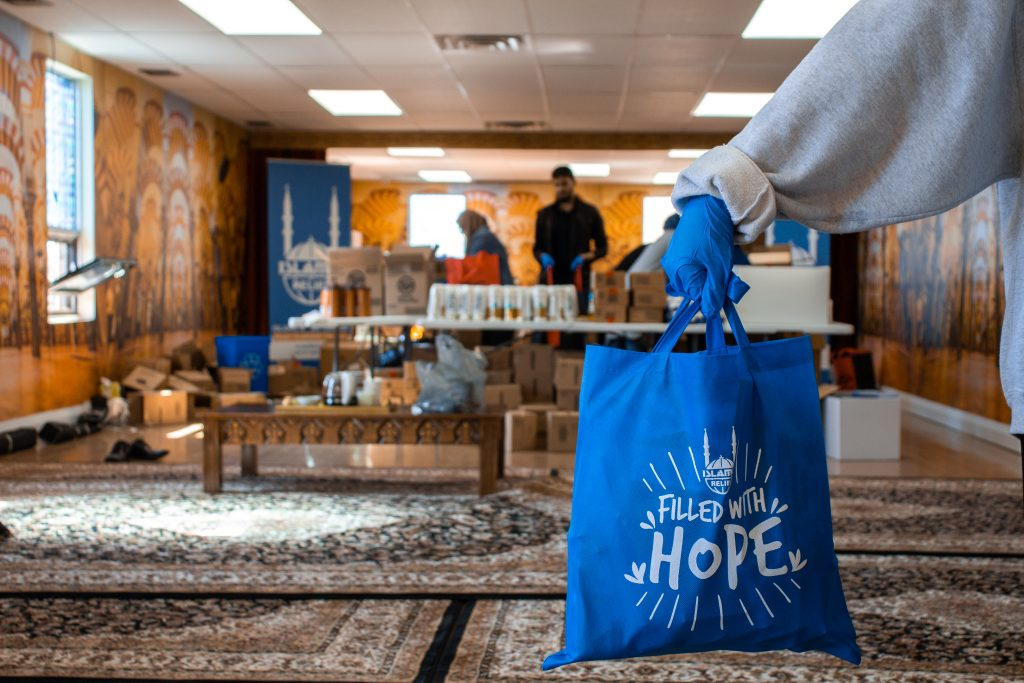 """A person holding up a blue """"filled with hope"""" bag"""